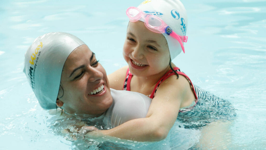 a swimway subsitute teacher teaching a young girl to swim