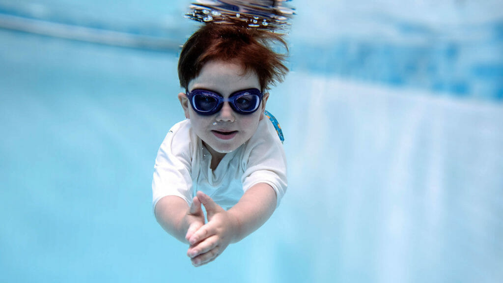 young boy swimming lessons underwater