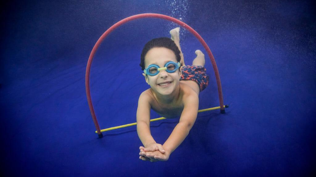 child swimming through a hoop underwater