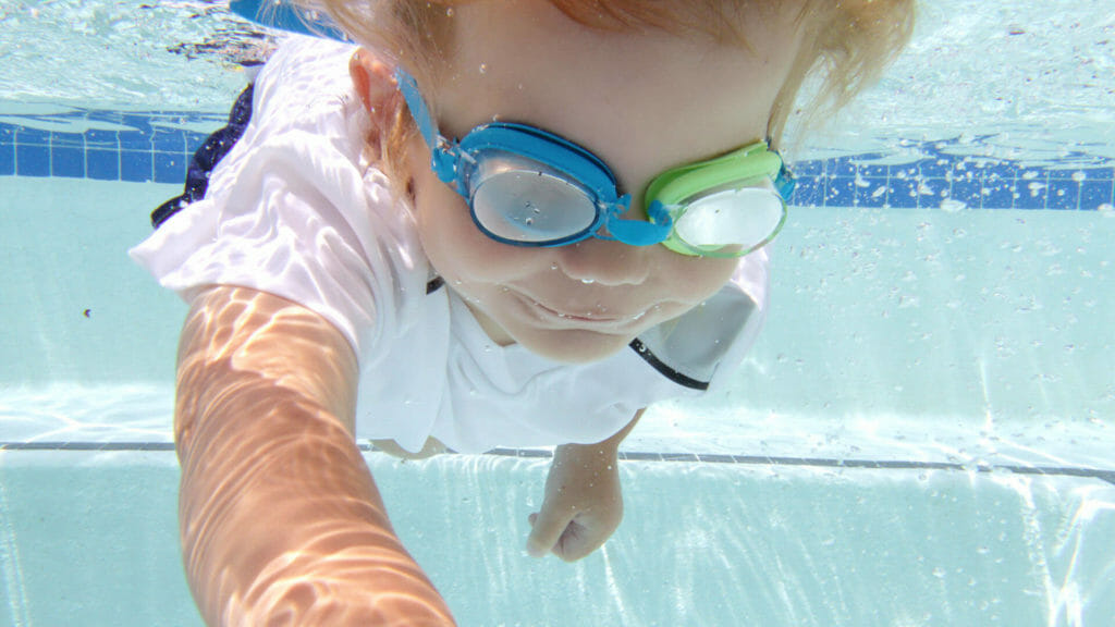 young child learning to swim