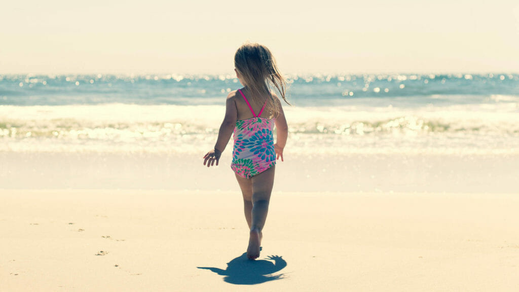 young child running on a beach