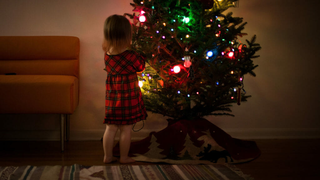 child looking for presents under a christmas tree